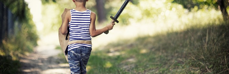 Little boy walks with a sword and a shield down a green path.