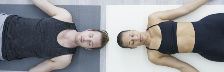 Two people meditating on the floor, they are a mirror of each other with their heads almost touching at the crown.