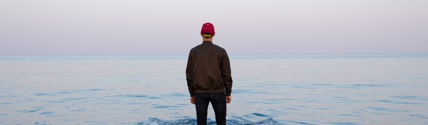 Man stands alone on a dock facing the water.