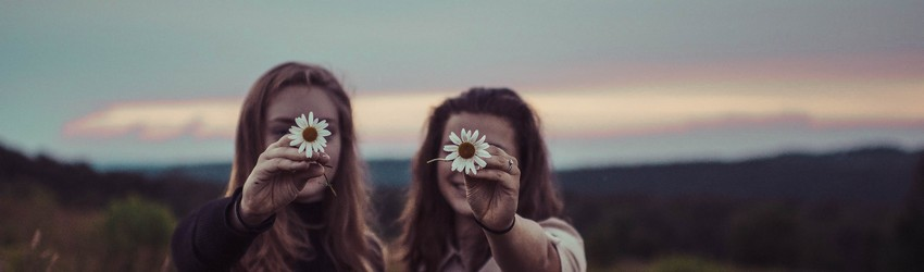 Two friends stand in a field holding daisies in front of their faces.