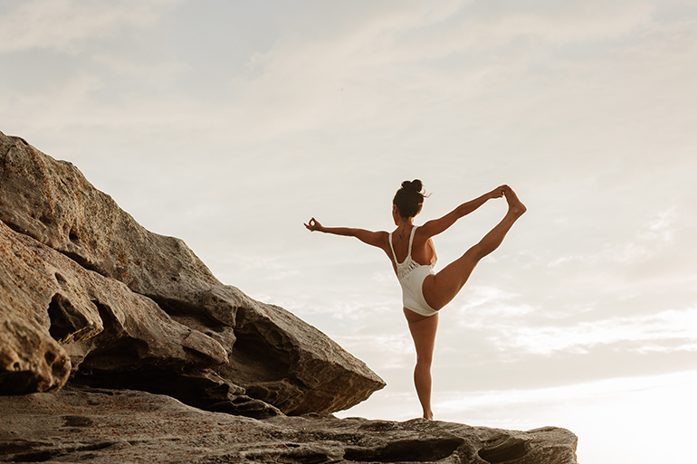 A woman stands on a cliff holding a balanced yoga pose.