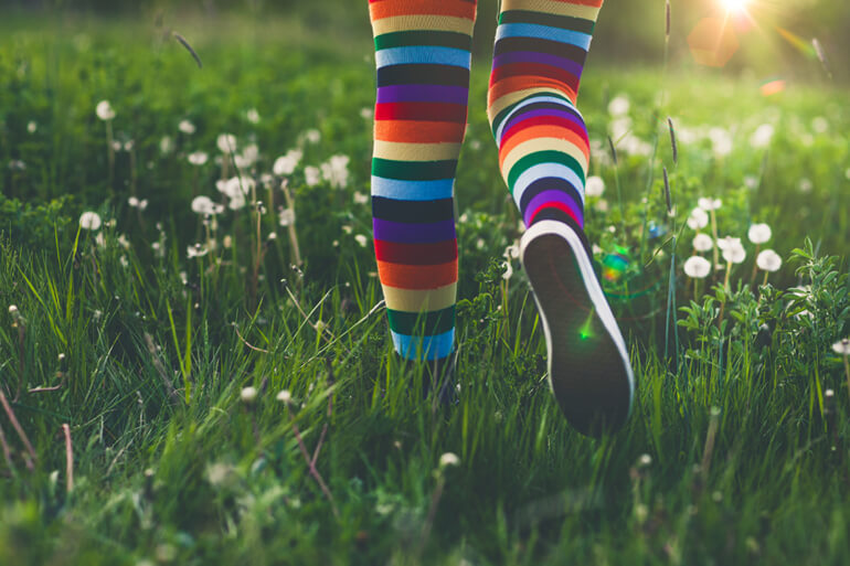 rainbow socks, woman running through field
