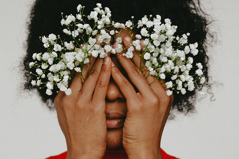 A black woman with natural hair us wearing a red sweater and holding babies breath flowers in front of her eyes.