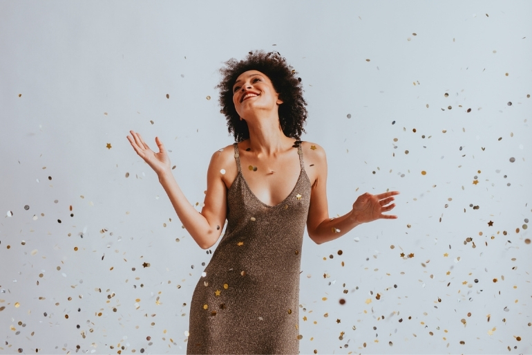 A woman dances around surrounded by golden confetti.