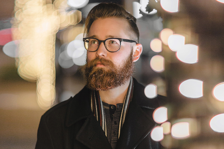 Man standing behind white fairy lights in a black coat. He wears big framed glasses and has a large beard.