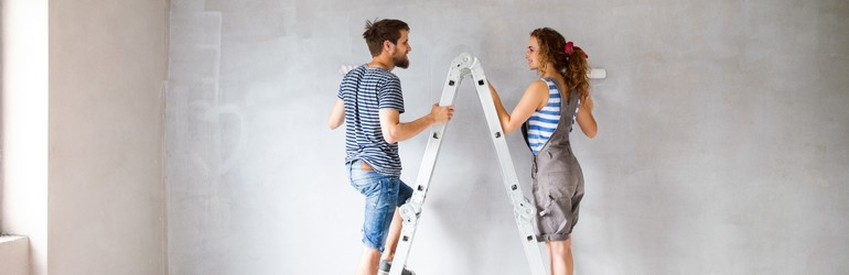 A man and a woman each stand on one side of a latter, they are painting a wall white.