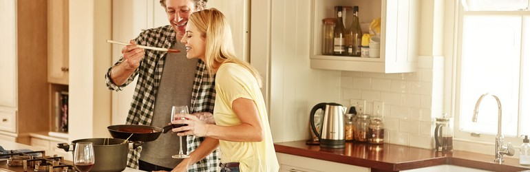 Man and woman make dinner, they man is holding the spoon up so the woman can taste test the sauce.