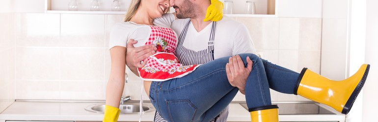 Man holds blonde woman in a bridal carry. She is wearing yellow rubber boots and gloves, they are both wearing aprons.