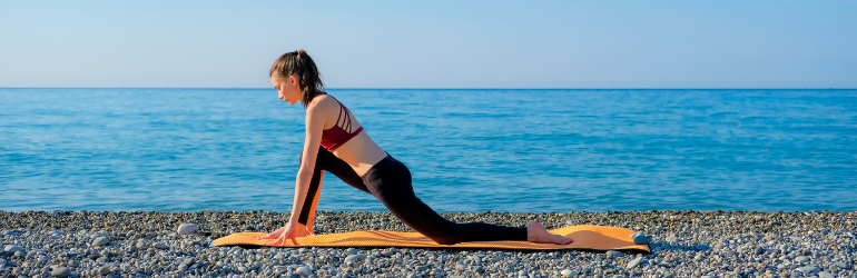 A woman does a low lunge on a beach.