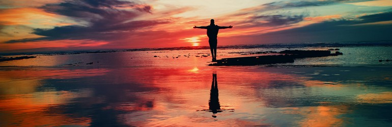 A person standing in front of a sunset, they have their arms open in acceptance.