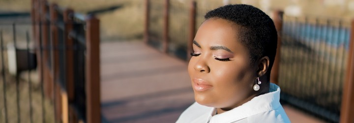 A black woman with very short hair breathes by a lake. Her eyes are closed.