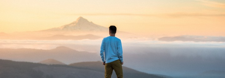 A man stands on a mountain looking out at the sunset on the horizon.