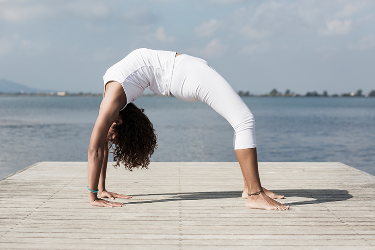 A person doing a yoga backbend on a dock. She is working at improving her skills.