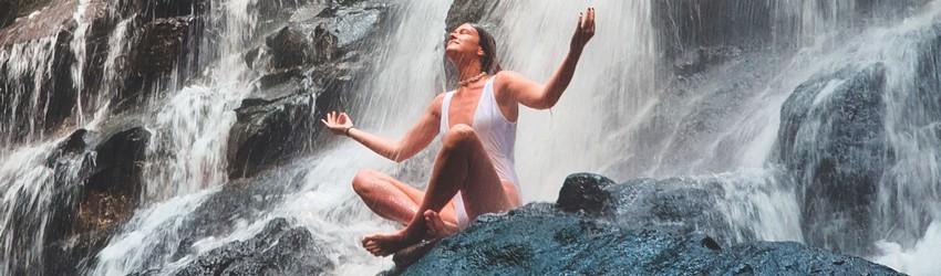 A woman meditates on a rock near a waterfall.