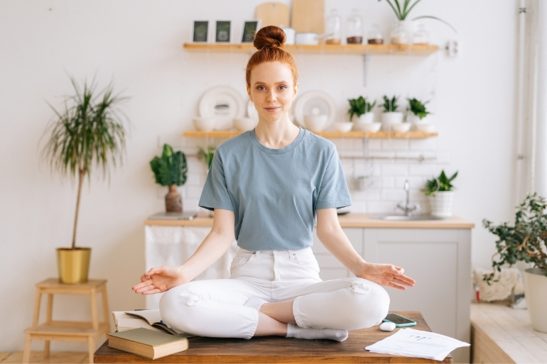A woman sits on her desk meditating. She is prepared for the new year.