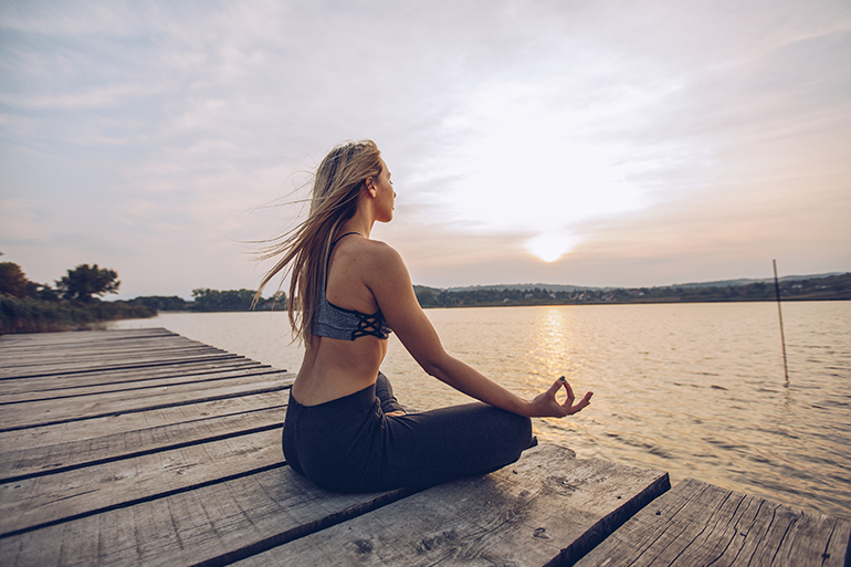 woman meditating on dock during summer