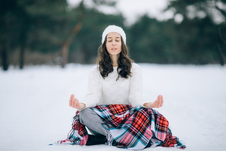 A woman meditates in the snow with a buffalo check blanket on.