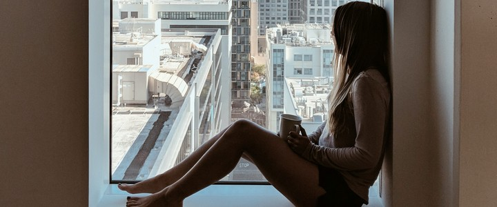 A woman sitting in a windowsill looking out at the city skyline. She is holding a mug in her hands as she sits in silent mindfulness.