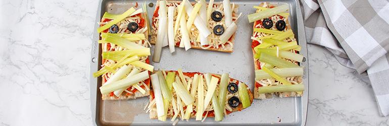 Mummy Pizzas on a baking tray.