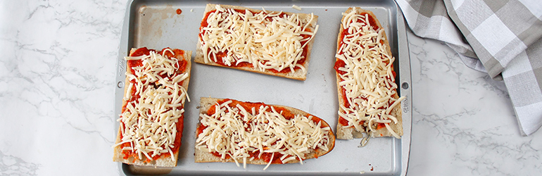 Long pizzas with mozza wrapped across.