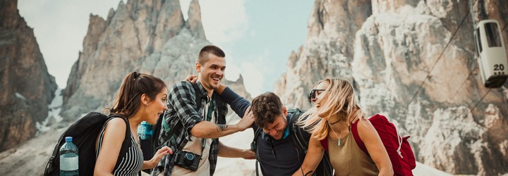 Two couples are laughing while on a hiking trip together.