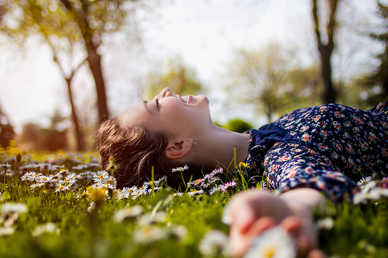 woman laying in flowers, flowers in a field, woman laying outside