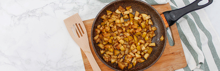 Baked apples with spices on it in a frying pan.