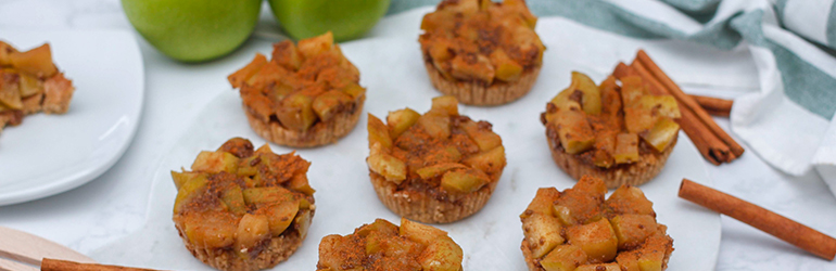 Mini apple pies from a higher up angle on a marble platter.