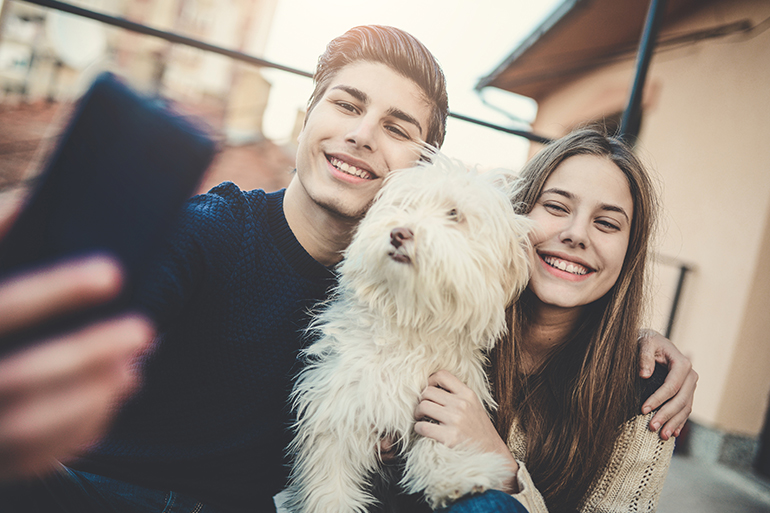brother and sister taking a selfie with their dog