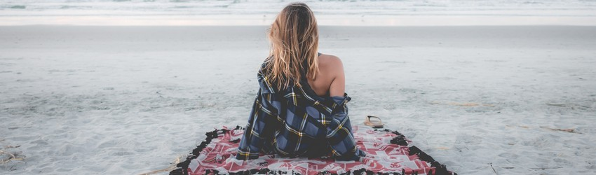 Woman pausing on a beach looking out at the ocean.