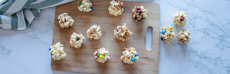 Sweet and salty popcorn balls on a cutting board.