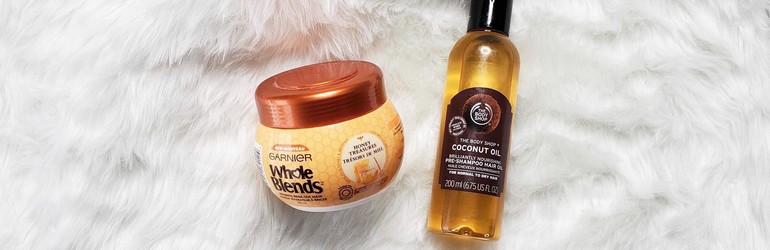 Garnier Whole Blends and The Body Shop Coconut Oil pre-shampoo are displayed on a white cloth.
