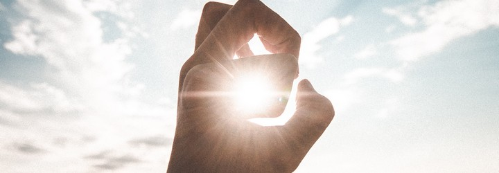 A person holds their fingers in a circle shape and lets the sun peak through.
