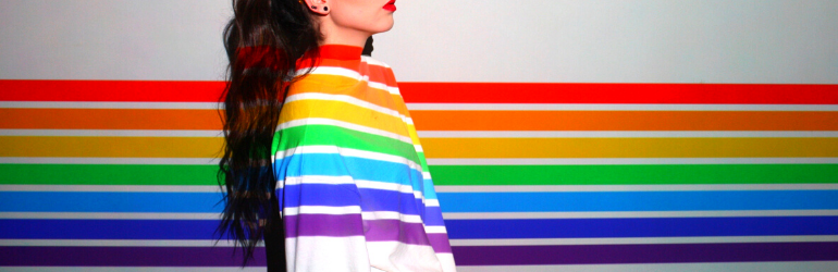 A woman stands in front of a rainbow wall with a rainbow shirt on so that she blends in.