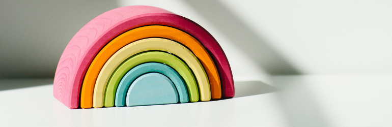 A clay rainbow is sitting on a white table.