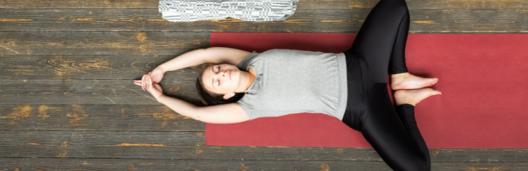 A woman lays back on a yoga mat in cobblers pose.