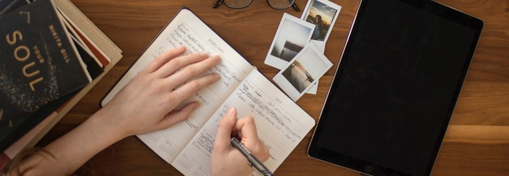 A person is writing out their stresses and emotions in their journal on a wooden desk. They are surrounded by photos and books.