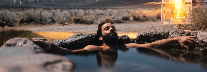 A man bathes in a hot spring under the stars. He is in the mountains and has his eyes closed.