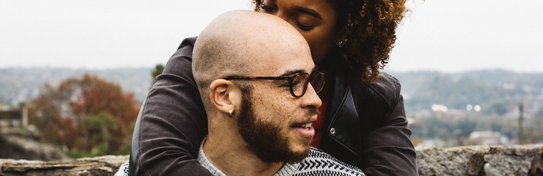 Two people sit holding each other on a hillside. A woman kisses the back of her bald partners head. He smiles and glances back at her.