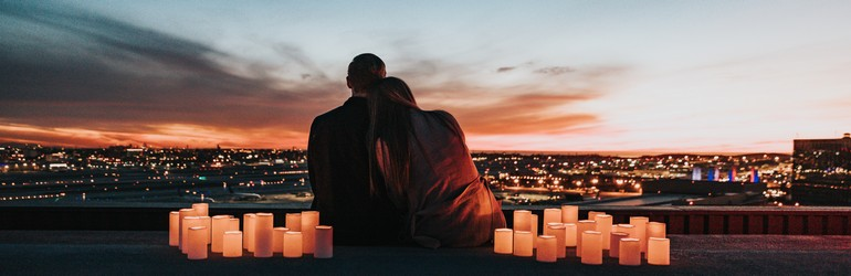 A couple sits on the edge of a hill looking at a city skyline. They are surrounded with romantic candles as the sun sets in front of them, they lean on each other for support.