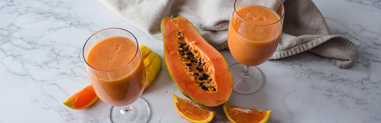 Two Papaya, Mango, and Orange Smoothies in glasses.