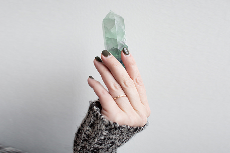 person holding blue crystal point