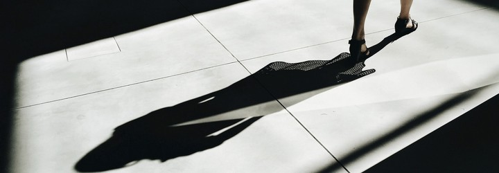 A person walks away from their shadow on a marble floor.