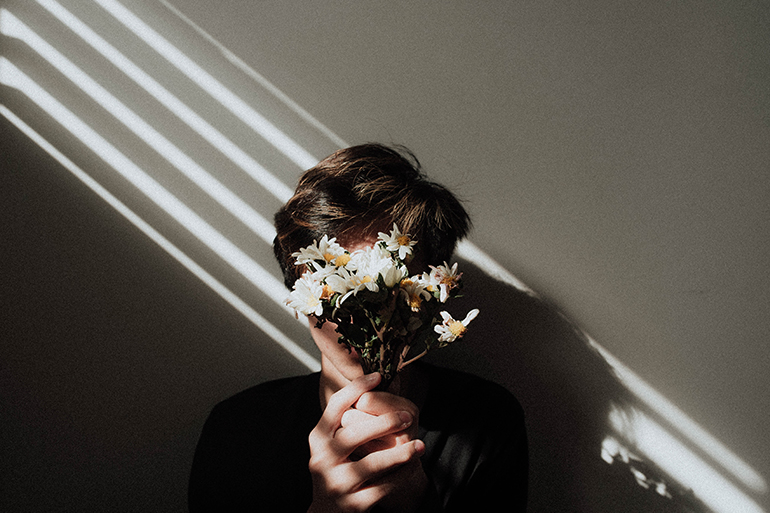 A person holds flowers in front of their face. A shadow from a window blind is also across their face.
