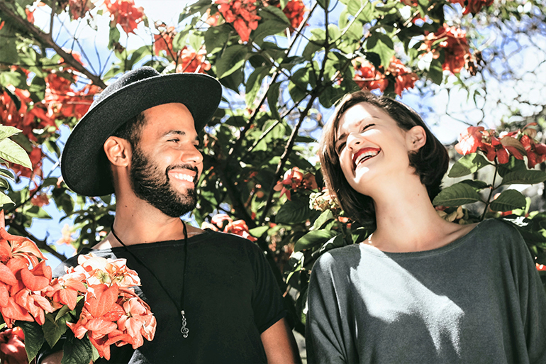 Two people stand next to each other in a red flower bush, they are laughing and looking at each other. The person on the left has a shaved head and is wearing all black with a floppy hat, the person on the right is wearing a grey shirt and has shoulder length brown hair.