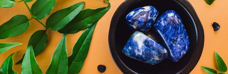 Sodalite Crystals in a bowl next to some green leaves. The crystals are blue.