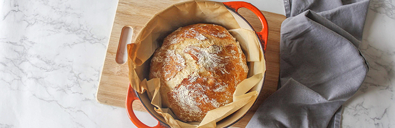 Sourdough bread risen in a dutch oven fully baked and dusted with flour.