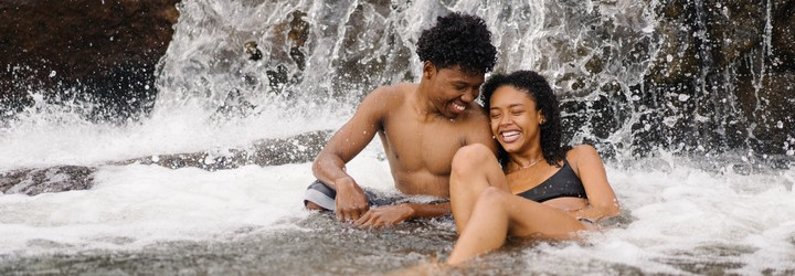 A couple sits in a waterfall laughing and cuddling with each other.