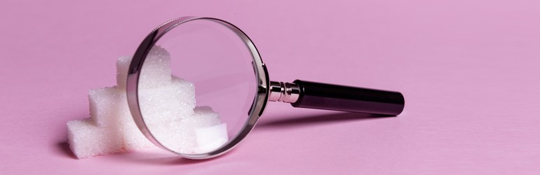 A magnifying glass focusing in on some sugar cubes on a purple background.