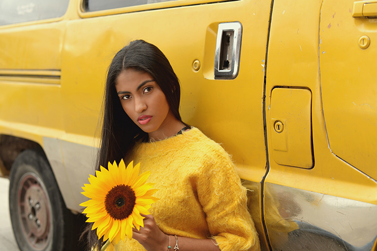 Woman wearing s yellow sweater holding a yellow sunflower in front of a yellow truck.
